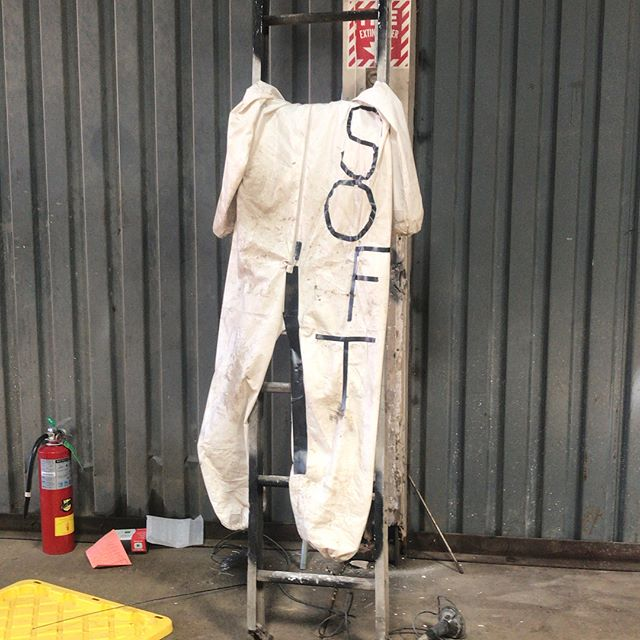 "Image description: A photo of a dirty white jumpsuit with the word ""soft"" written in capital sans serif letters."