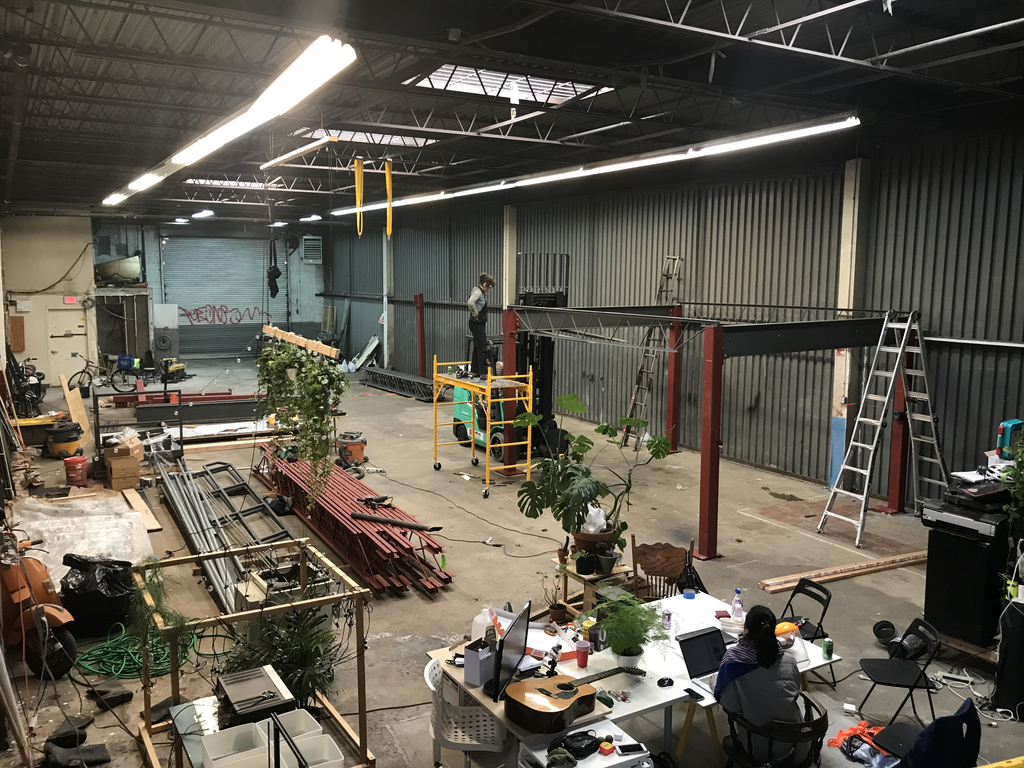 Soft Surplus members collectively building the mezzanine at their studio space.