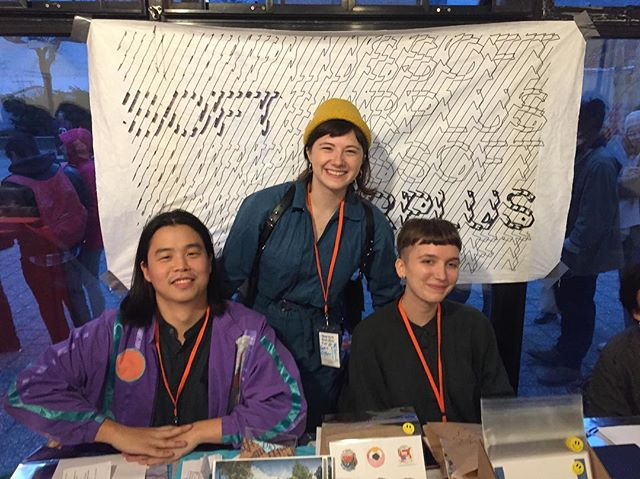 Soft Surplus members tabling at the New York Tech Zine Fair. Image description: Three people sit and stand behind a table filled with zines and other printed matters, happily smiling and looking at the camera.